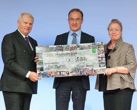BBU-Vorstände Maren Kern (rechts) und Dr. Klaus-Peter Hillebrand (links) überreichten den bunten Spendenscheck an DESWOS-Vorstand Dr. Christian Lieberknecht.