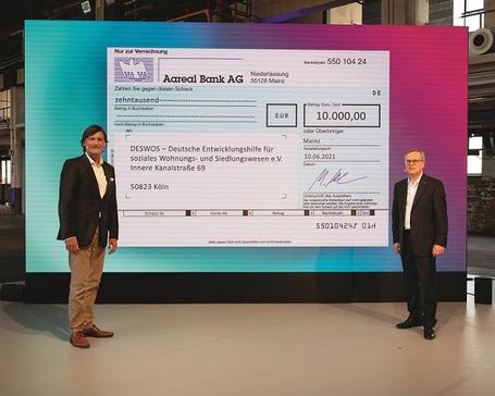 Dr. Manfred Alflen präsentierte Gerhard Müller bei der digitalen Veranstaltung den wohl größten Spendenscheck für die DESWOS (von rechts), Foto: Angelika Stehle, Wiesbaden