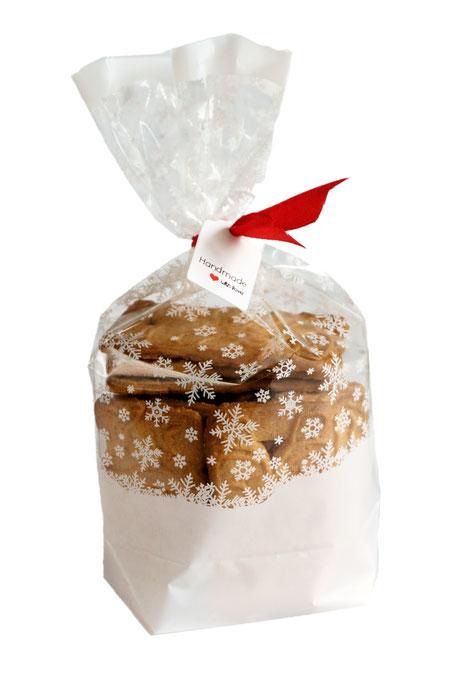 Weihnachtliche Kekstüte mit weißen Schneekristallen als Dekobeispiel gefüllt mit Keksen, roter Schleife und handmade with love Etikett.