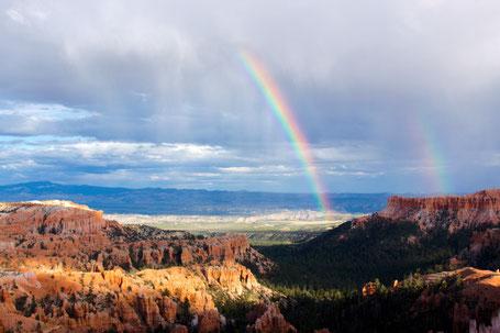 Ein Regenbogen kommt aus den Wolken und führt in eine Naturlandschaft