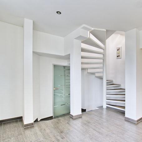 Immobilienfoto: In weiß gehaltenes Treppenhaus mit Wendeltreppe