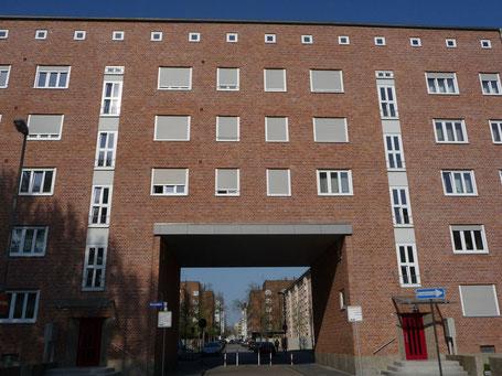 Streng spiegel-symmetrisch, fünfstöckig mit hohen Durchlässen in der markanater Backstein-Fassase: Die Arbeiter-Wohnungen der Westend-Siedlung waren zwar klein, aber für damalige Verhältnisse komfortabel ausgestattet.