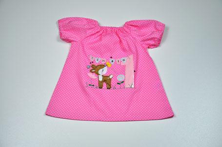Baumwolltunika aus rosa Baumwolle mit weißen Punkten. Au dem vorderteil wurde ein reh gestickt. Neben dem Reh ist rechts eine Geburtstagszahl.