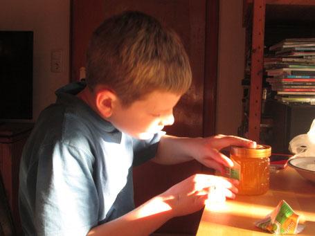 Während der Bruder lieber draußen an den Bienen arbeitet, übt sich Joel (9) mit Begeisterung am Etikettieren des eigenen Honigs. Der Erlös aus dem Verkauf wird wie die Arbeit mit dem Bruder geteilt!