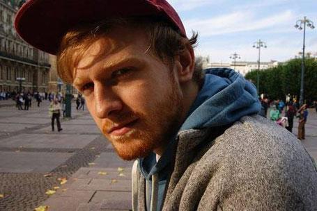 Johannes Deistung -mit rotem Haar und roter Kappe auf dem Kopf- sitzt in einer Fußgängerzone und schaut in die Kamera.