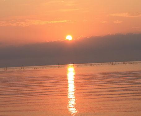 秋分の日、朝日が湖面に黄金の光を照らす