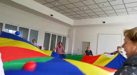 Momentaufnahme aus einer kurzen Videoaufzeichnung: Bälle werden auf einem großen, bunten Schwungtuch in Bewegung gehalten.