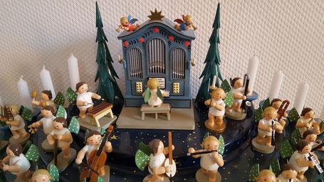 Ein Engels-Orchester aus kleinen Holzfiguren gibt ein Konzert. Im Hintergrund eine historische blaue Holzorgel, an der ein Engelchen sitzt.