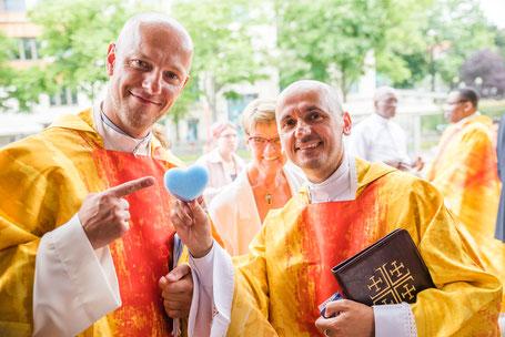 Kaplan und Pfarrer  mit dem blauen Herzen des neuen Pfarrlogos