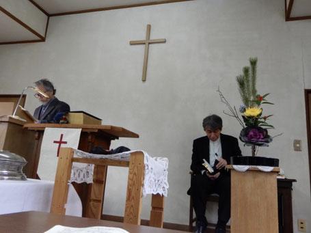 2020年1月5日の十文字平和教会の礼拝のひとこま 左 司式者の満さんです。新年の献花が見事ですね。