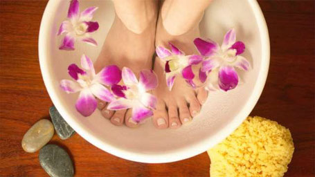 A photo of feet soaking pre lomilomi massage in a bowl of water with flowers and stones around it.