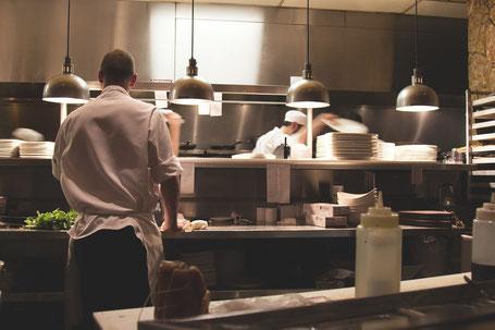 Edelstahlküche mit arbeitenden Köchen