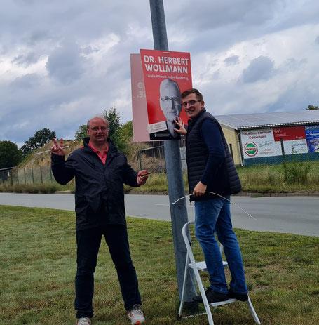 v.r. Robert Drews und Thorsten Gericke zeigen vollen Einsatz beim Plakate aufhängen.