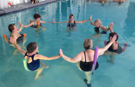 Karen practicing standing pigeon pose with her community in the water. She is the one with a big smile on her face! (mid center upper circle)