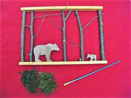 décoration en bois d'un cadre en cours de finition, représentant une maman ours et son petit. De la mousse végétale naturelle est posée devant, car sera rajoutée sur la décoration