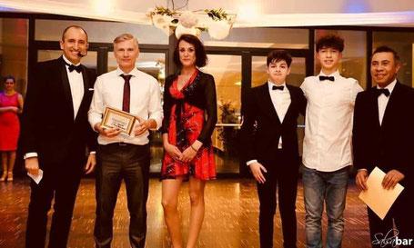 Eva Grebner überreicht auf dem Salsaball dem Gewinner der Tombola einen Gutschein für einen Spanischkurs