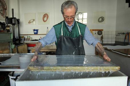 John Gerard schöpft Papier von Hand aus der Bütte in seiner Papierwerkstatt