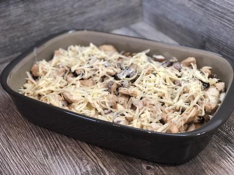 Auflaufform aus Ton in grauer Farbe mit Champignons und Schnitzel befüllt und mit Käse bestreut