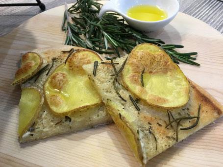 Kartoffel-Rosmarin-Pizza fertig angerichtet auf Holtplatte mit Rosmarin und Olivenöl-Schälchen