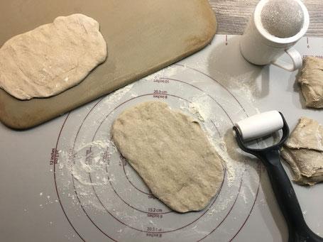 Backmatte mit Teig der zu kleinen Fladen ausgerollt wird.