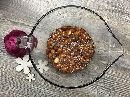 Mandeln in Glaschüssel mit flüssigem Zucker