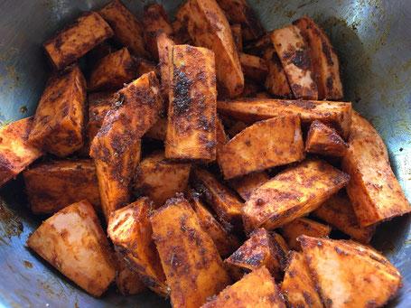 Süßkartoffelspalten mit der Gewürzmischung vermischt in einer Metallschüssel