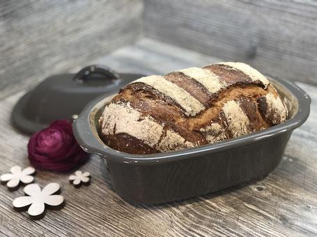 Frisch gebackenes Brot in einem Brotbacktopf liegend auf Arbeitsplatte