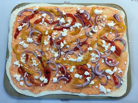 Pizza vor dem backen mit Gemüse und roter Sauce auf dem Tonbackstein von Pampered Chef