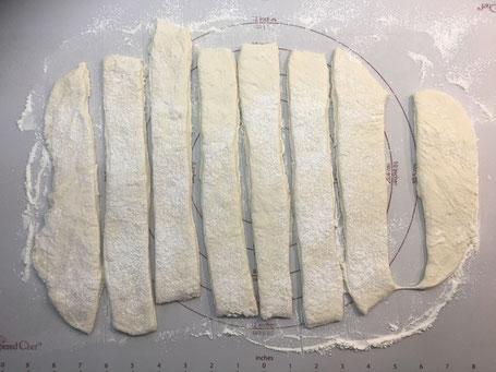 Brötchenteig auf einer Backmatte ausgerollt und in Streifen geschnitten