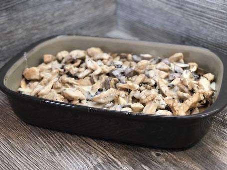 Auflaufform aus Ton in grauer Farbe mit Champignons und Schnitzel befüllt