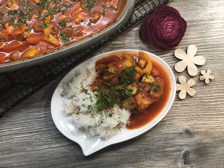 Teller mit Hähnchenfleisch, Soße und Reis angerichtet