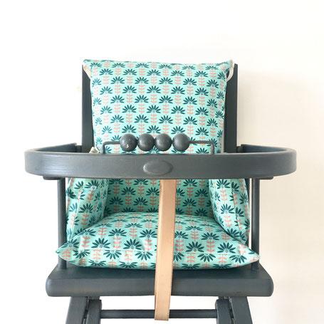 Cette image représente un coussin de chaise haute en coton enduit Vert pour chaise haute combelle