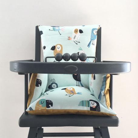 cette image représente un coussin de chaise haute aux motifs de toucan compatible avec la chaise haute Combelle