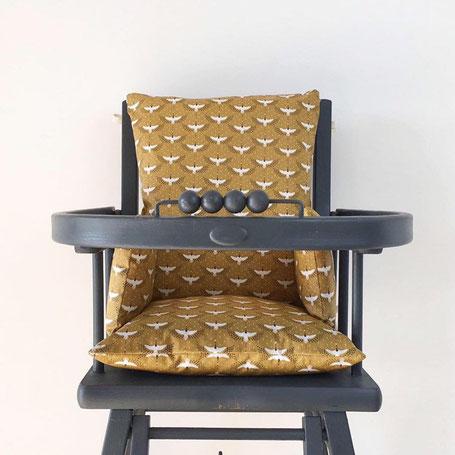 Cette image représente un coussin de chaise haute de couleur camel pour chaise haute en bois