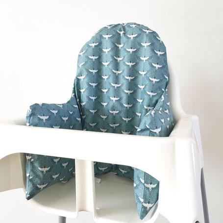 Cette image représente un coussin de chaise haute pour chaise haute Ikea bleu avec des oiseaux grues