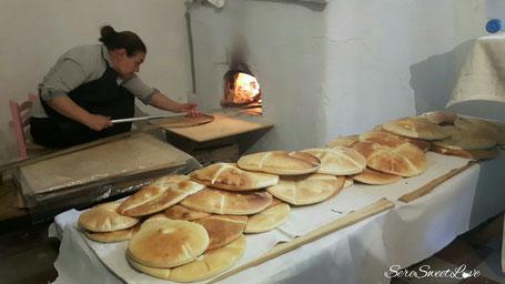 donna orgolese che inforna il pane tipico nel forno a legna