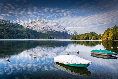 Boote im Silsersee und verschneite Berge im Hintergrund die sich im See spiegeln
