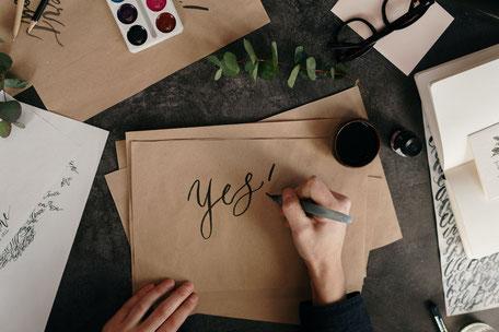 Auf einem Blatt Papier wird in künstlerischer Schrift das englische Wort für JA geschrieben.