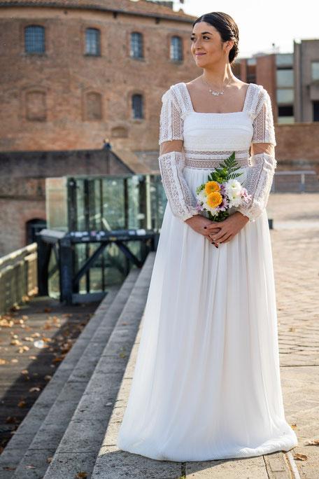 Robe de mariée fluide, ceinture en dentelle transparente séparant le haut recouvert de dentelle et jupe plissée