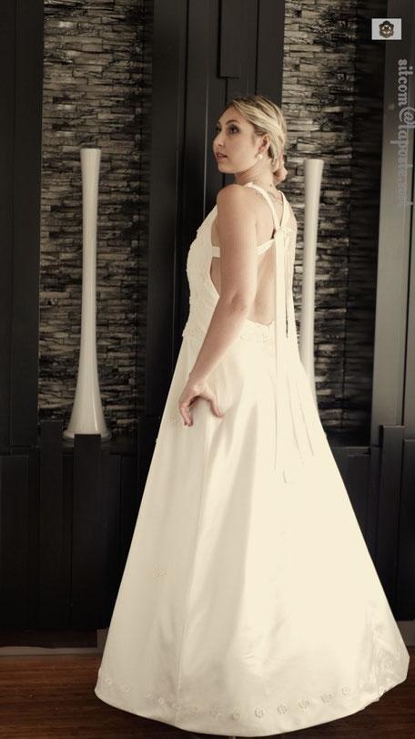 Robe de mariée dos dénudé maintenu par quatre longs liens, jupe évasée bordée en bas de fleurs rappelant le haut devant du bustier tout en dentelle