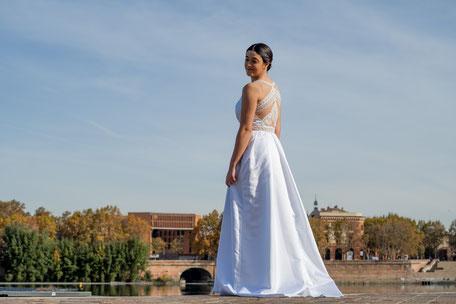Robe de mariée en satin duchesse, dos bustier nu recouvert de dentelle, jupe à pli creux