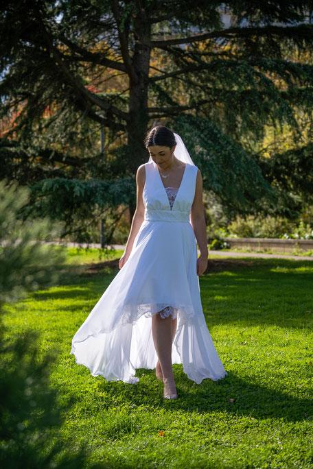 Robe de mariée fluide tout en transparence, ceinture en dentelle séparant le bustier et la jupe