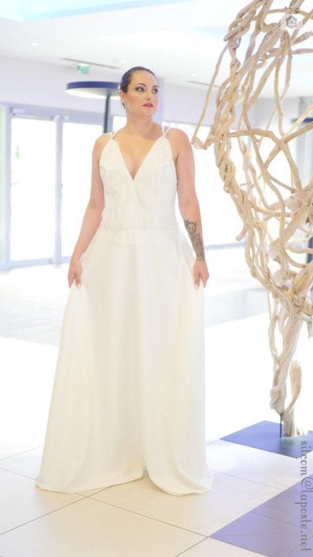 Robe de mariée, bustier recouvert de dentelle avec une encolure en V maintenu par 3 fines bretelles qui vont s'entrelacer sur un haut de dos nu, jupe légérement évasée dans un tissu fluide