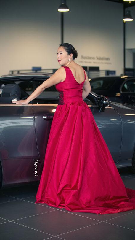 Robe de mariée rouge recouverte d'une large dentelle uniquement sur le devant au niveau de la taille, jupe à plis plats terminée par une longue traîne