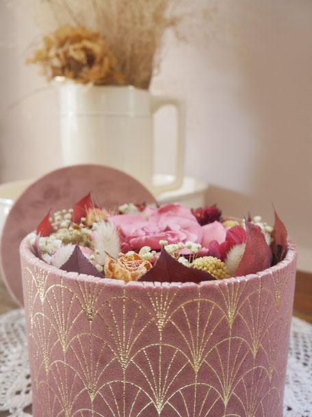 Jolie boite en velours inspirée des boites à chapeaux anciennes. Mélange de fleurs séchées et stabilisées dans les teintes de vieux rose, blush, bordeaux et doré. Composée d'hortensia, gypsophile, gardénia stabilisés ainsi que de fleurs séchées.