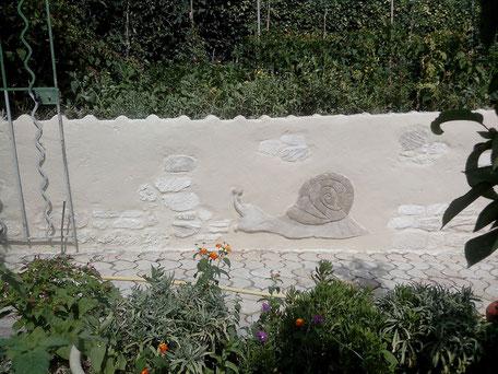 Muret de clôture en enduit imitation pierre vue avec crépis gratté et décoration escargot