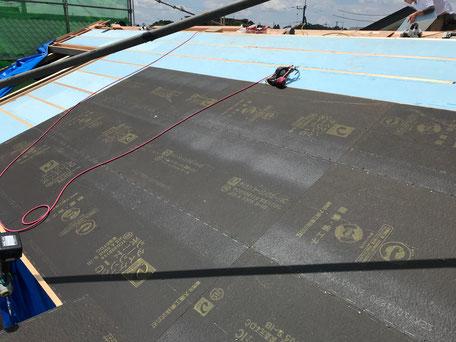 断熱材の上にシージングボードという黒い建材を施工している途中の様子