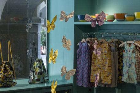 Schaufenster des einLaden Bern. Verkauft werden Kinderkleider, Kinderspielzeug, Wohnaccessoires, Geschenke, Krüge und Stofftaschen.