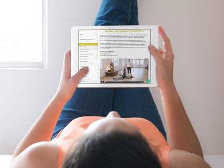 Frau mit Tablet sieht Yogatherapie Online-Kurs an