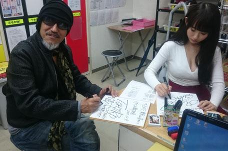 事務所でサインを書いてくれてるトージロー監督と美咲結衣さん。